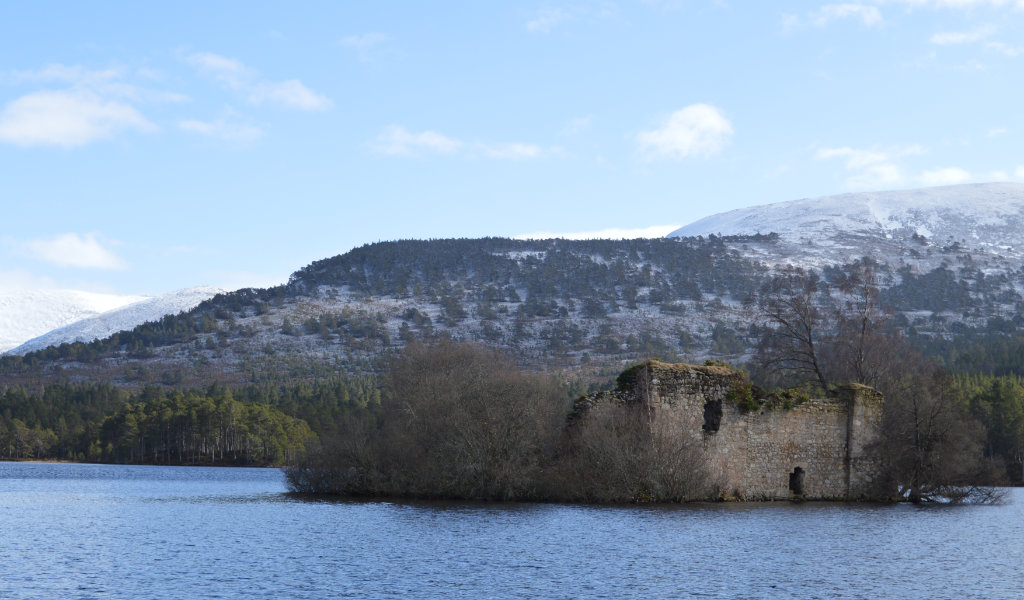Loch an Eilein Castle with snow capped mountains